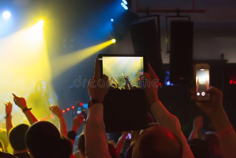 el grabar del smartphone y de la tableta del concierto fotografía de archivo
