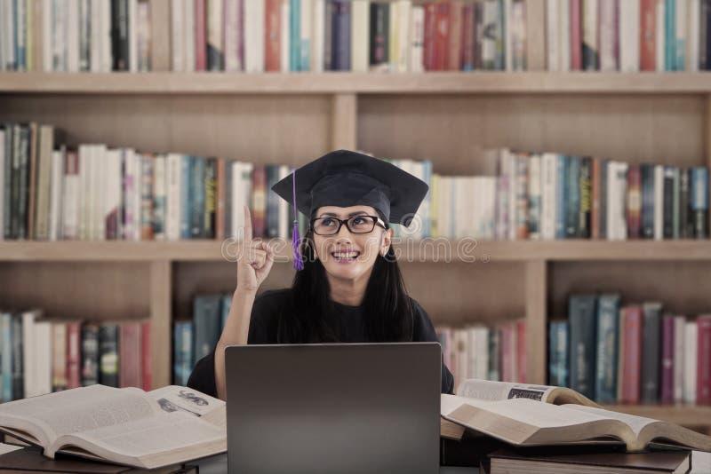 El graduado asiático de la hembra tiene idea en la biblioteca imagen de archivo