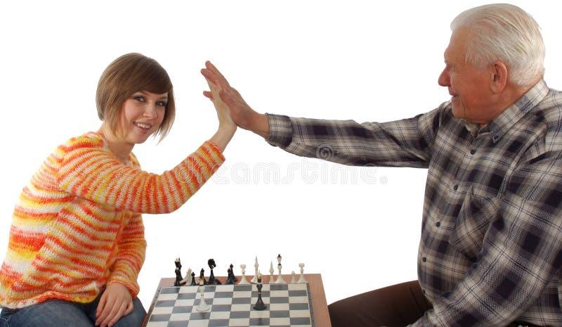 El Grandad y la nieta hacen un compromiso en ajedrez imagen de archivo