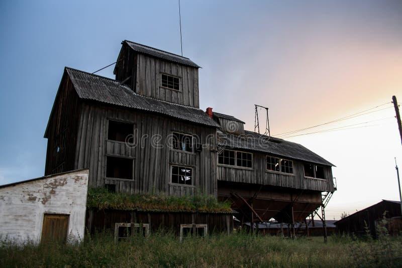 El granero abandonado viejo en los rayos de la puesta del sol, como un castillo móvil Cerca de madera en el primero plano imagenes de archivo