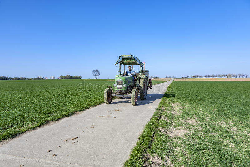 El granjero en su tractor monta detrás después de arar su campo fotos de archivo