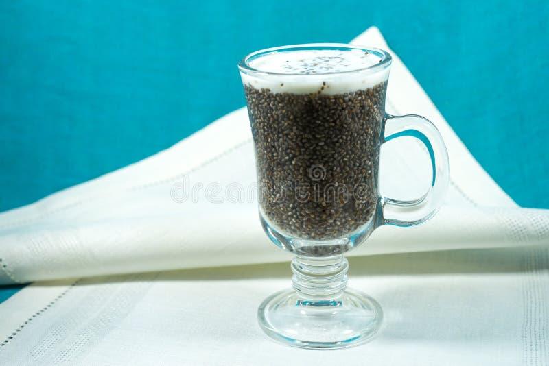 El grano Chia se mezcló con el jugo y la leche en la taza de cristal en un paño ligero de la tela fotos de archivo libres de regalías