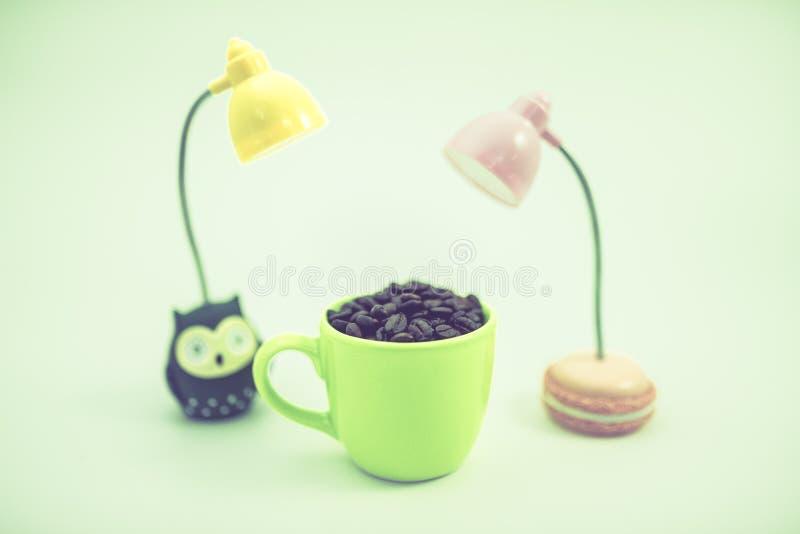 El grano de café en la taza verde con las lámparas del LED, fondo blanco, s imagen de archivo libre de regalías