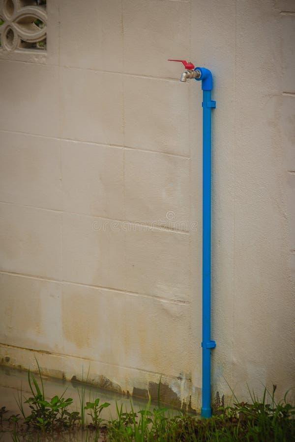 El grifo de bronce sucio del campo conectó con el tubo azul del PVC en blanco foto de archivo libre de regalías