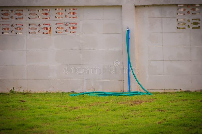 El grifo de bronce sucio del campo conectó con el tubo azul del PVC en blanco fotografía de archivo
