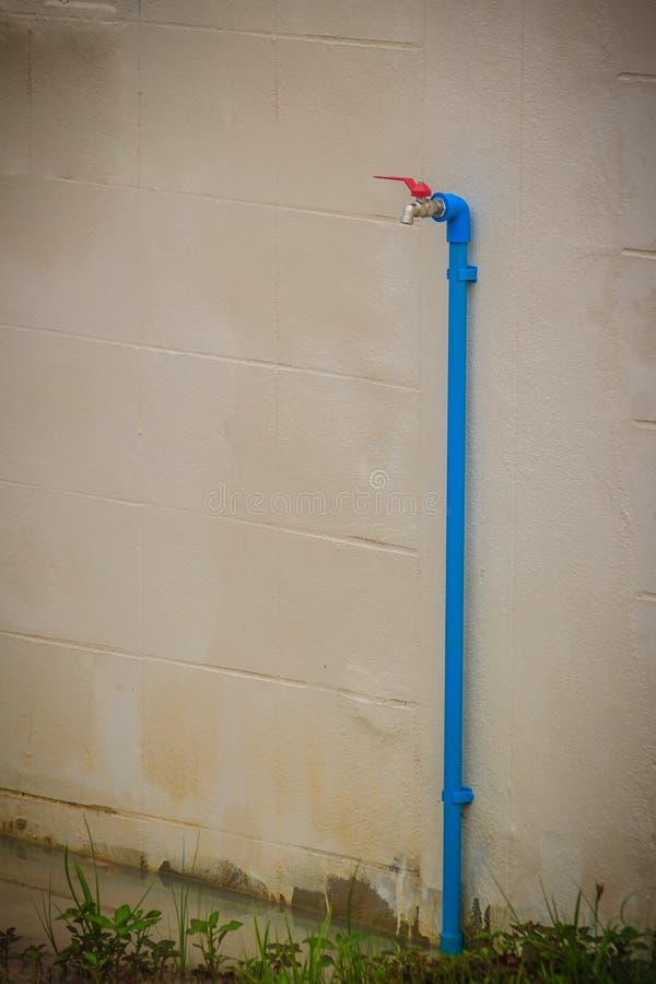 El grifo de bronce sucio del campo conectó con el tubo azul del PVC en blanco fotografía de archivo libre de regalías