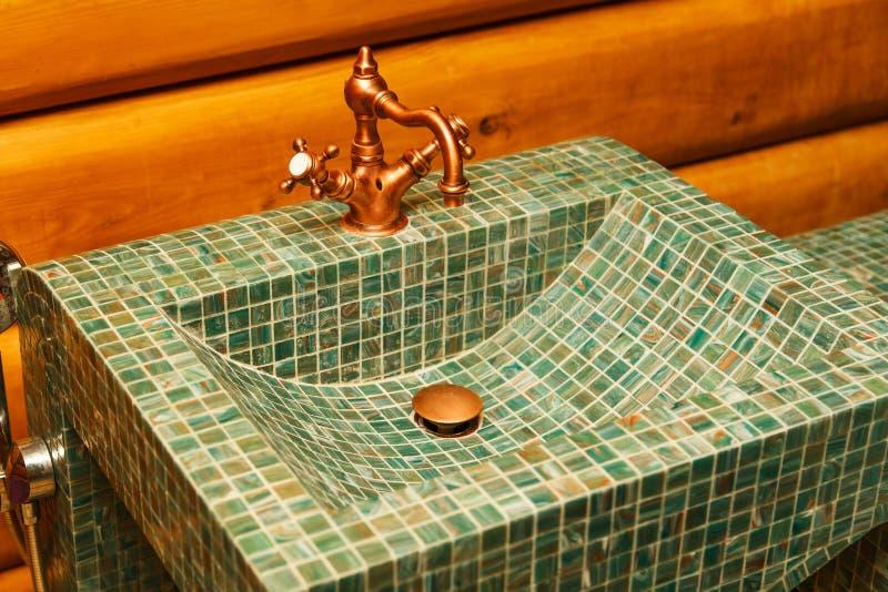 El grifo de cobre en un lavabo hecho de la teja de mosaico verde foto de archivo libre de regalías