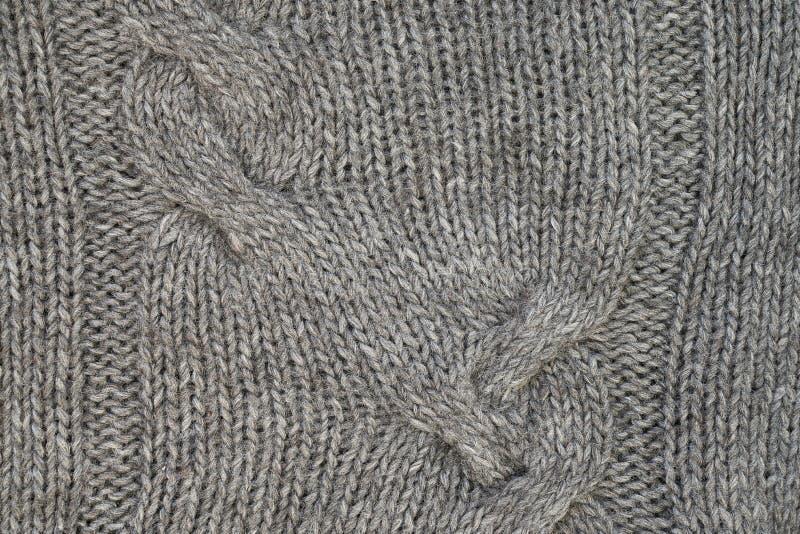 El gris hizo punto textura con un modelo de alivio Géneros de punto hechos a mano Fondo fotografía de archivo
