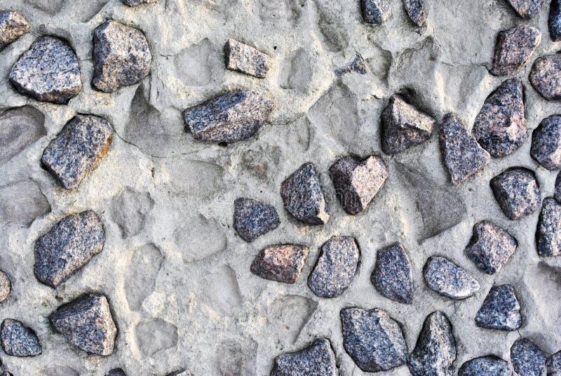 El gris machacó piedras en la pared del cemento y de las impresiones de caído fotografía de archivo libre de regalías