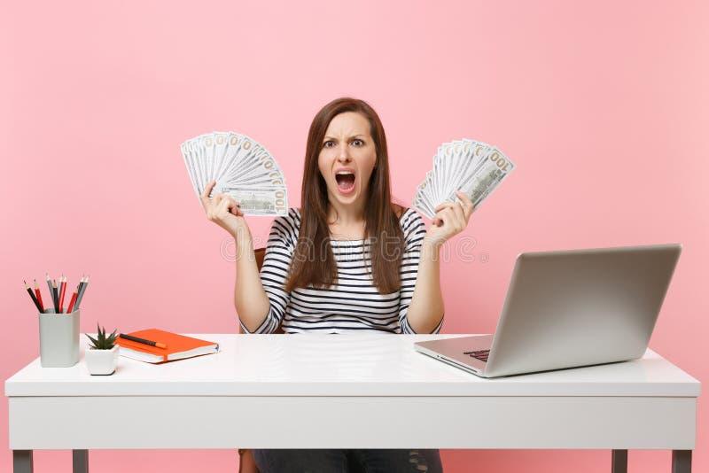 El grito irritado enojado joven de la mujer separó las manos con las porciones del paquete de dólares cobra el trabajo del dinero fotos de archivo libres de regalías