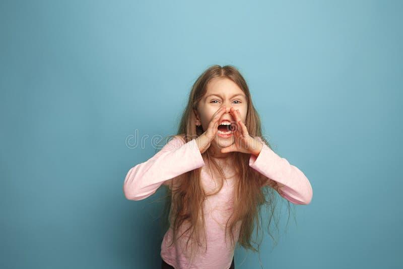El grito Muchacha adolescente en un fondo azul Expresiones faciales y concepto de las emociones de la gente imagen de archivo libre de regalías
