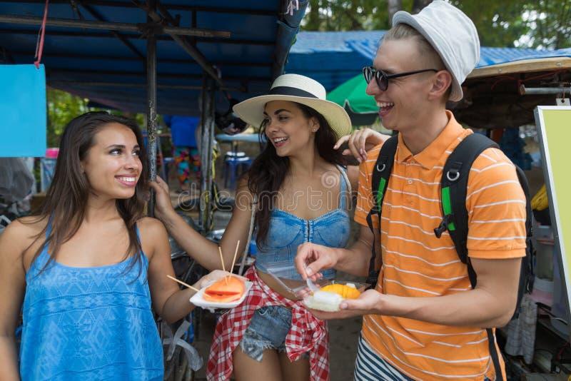 El grupo alegre de amigos come las frutas frescas que exploran a gente joven feliz asiática de los turistas de los cafés de la ci fotos de archivo libres de regalías
