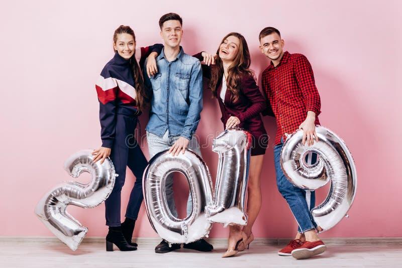 El grupo alegre de amigos de dos muchachas y dos individuos vestidos en ropa elegante están sosteniendo los globos en la forma de fotos de archivo libres de regalías