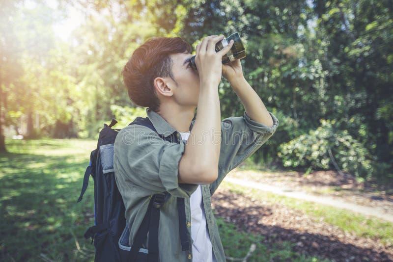 El grupo asiático de gente joven que camina con las mochilas de los amigos que camina junto y que usa los prismáticos, relaja tie fotos de archivo libres de regalías