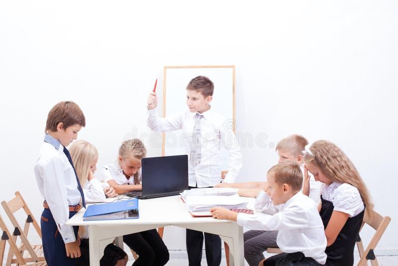 El grupo de adolescentes que se sientan en un negocio imagen de archivo