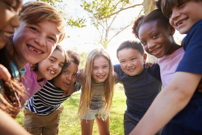 El grupo de alumnos sonrientes se inclina adentro al abarcamiento de la cámara imágenes de archivo libres de regalías