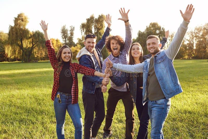 El grupo de amigos conect? el pulgar para arriba en el parque foto de archivo
