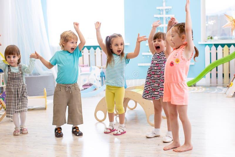 El grupo de amigos emocionales con sus manos aumentó Los niños tienen pasatiempo de la diversión en guardería foto de archivo