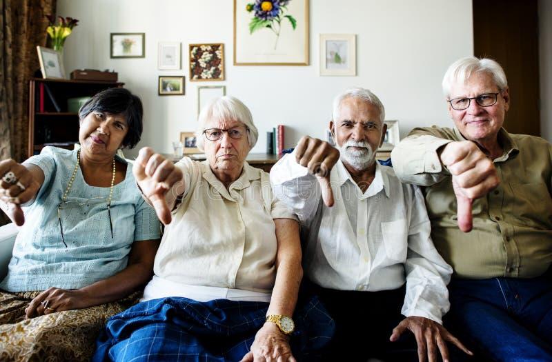 El grupo de amigos mayores que gesticulan los pulgares abajo firma imagen de archivo libre de regalías