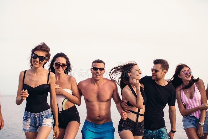 El grupo de amigos que caminan en la playa, divirtiéndose, el transporte por ferrocarril de la mujer encendido sirve, las vacacio fotografía de archivo libre de regalías