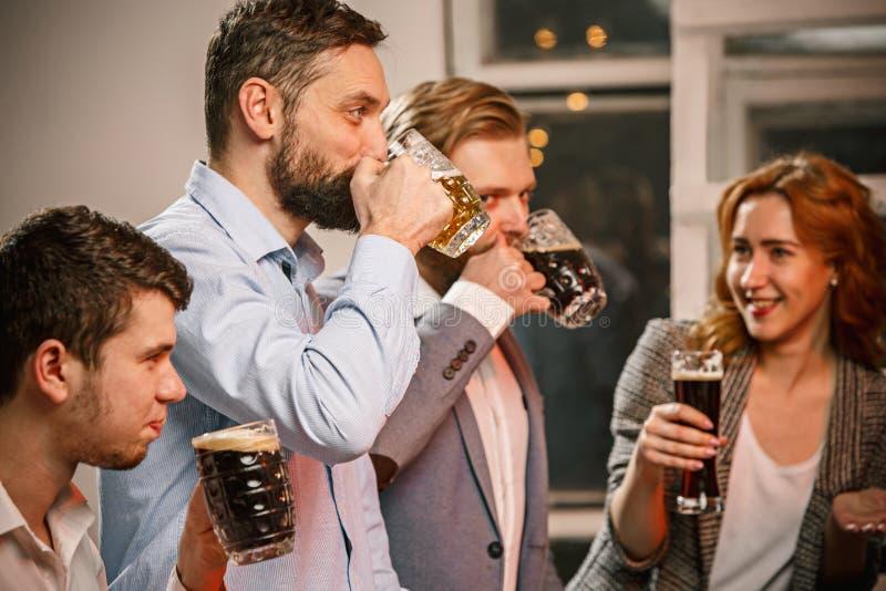El grupo de amigos que gozan que iguala bebe con la cerveza fotografía de archivo