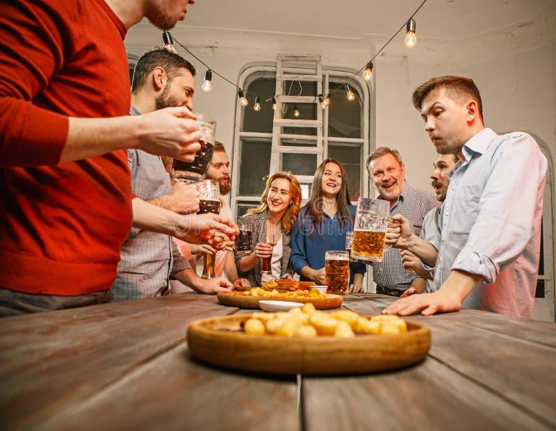 El grupo de amigos que gozan que iguala bebe con la cerveza imagen de archivo
