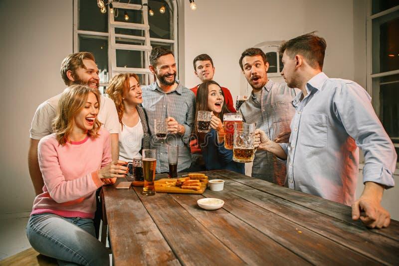 El grupo de amigos que gozan que iguala bebe con la cerveza fotografía de archivo libre de regalías