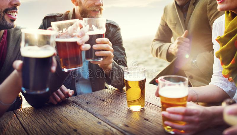 El grupo de amigos que hablan y tiene cervezas fotos de archivo