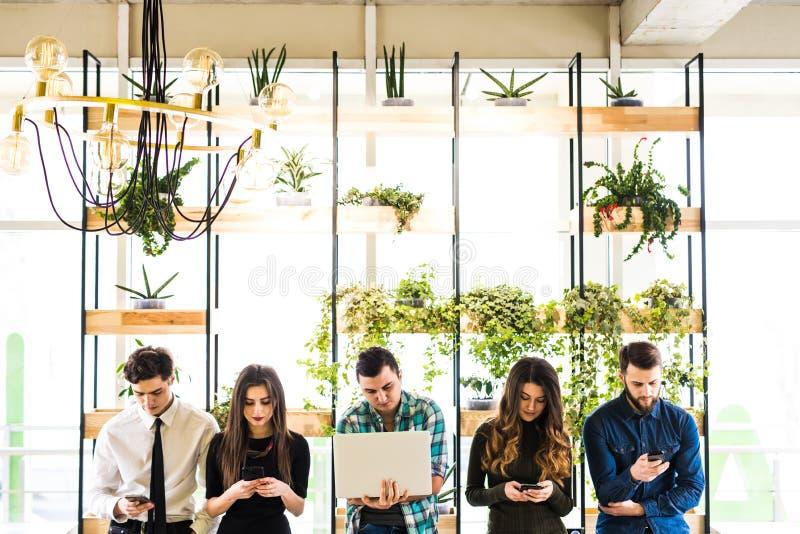El grupo de amigos que se colocan en la tabla y todo el mundo utilizan sus divices en sitio moderno de la oficina Junto diversión fotografía de archivo libre de regalías