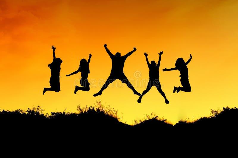 El grupo de amigos salta en el top de la montaña imagenes de archivo