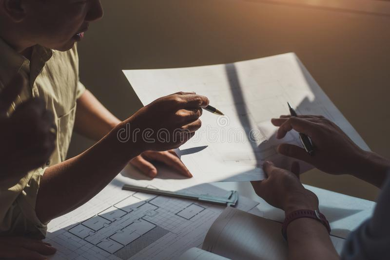 El grupo de arquitectos que discuten con los modelos planea en diseño de la oficina Concepto de la construcción y de la estructur foto de archivo
