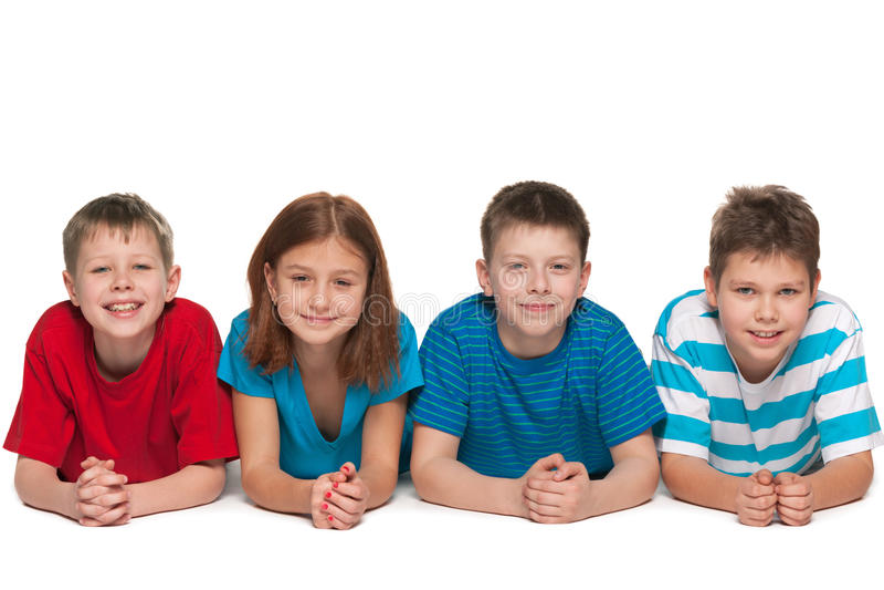 Cuatro niños están mintiendo en el piso imagen de archivo