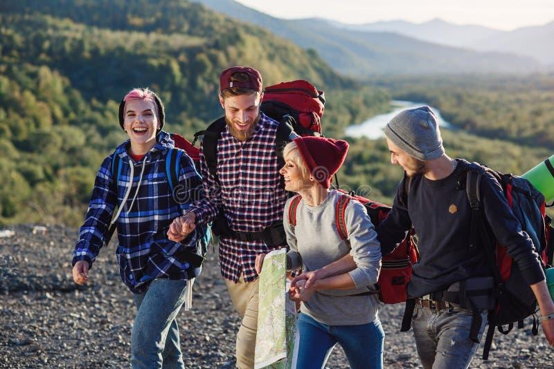 El grupo de cuatro viajeros felices está caminando con el mapa y está intentando descubrir la manera correcta en el top de la mon imagen de archivo libre de regalías