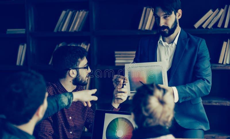 El grupo de dise?adores discute la paleta de colores en una oficina moderna imágenes de archivo libres de regalías