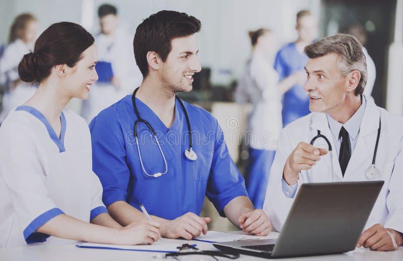 El grupo de doctores con el ordenador portátil discute la operación fotos de archivo libres de regalías