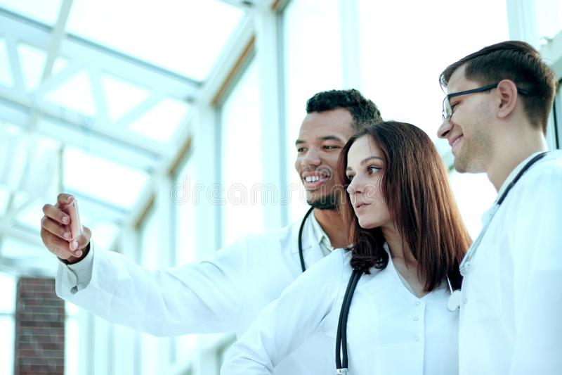 El grupo de doctores interna tomando selfies en el pasillo del hospital fotos de archivo libres de regalías