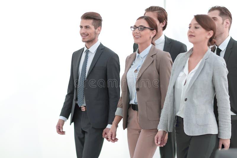 El grupo de empleados de la compañía pasa con confianza a través del pasillo de la oficina imagen de archivo libre de regalías