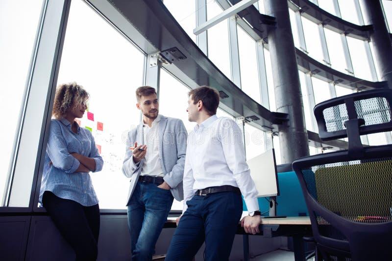 El grupo de empresarios jovenes est? buscando una soluci?n del negocio durante proceso del trabajo en la oficina Hombres de negoc fotografía de archivo libre de regalías