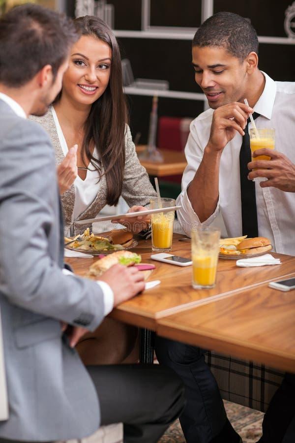 El grupo de empresarios jovenes goza en almuerzo en el restaurante fotografía de archivo