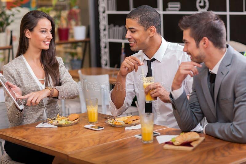 El grupo de empresarios jovenes goza en almuerzo en el restaurante imagen de archivo libre de regalías