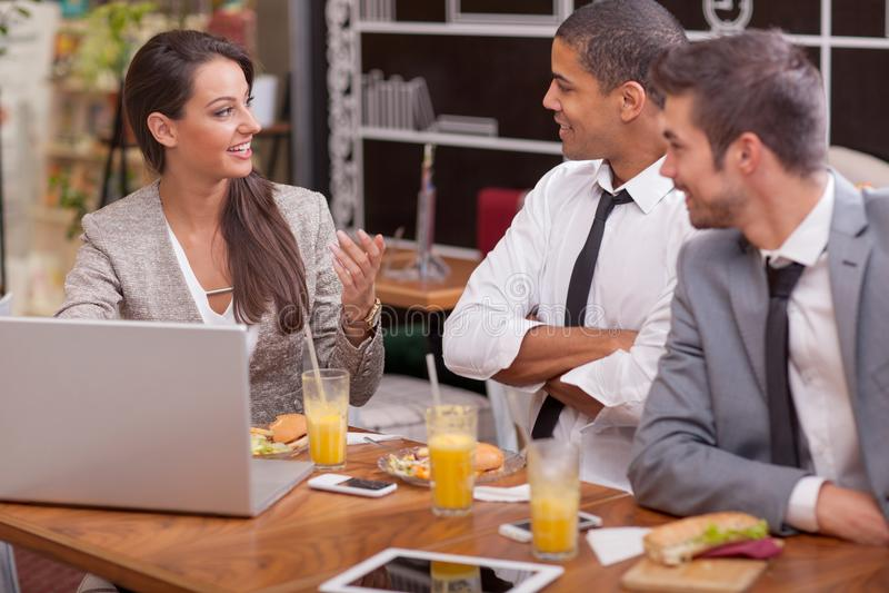 El grupo de empresarios jovenes goza en almuerzo en el restaurante fotos de archivo libres de regalías