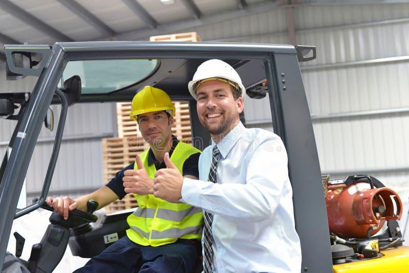 El grupo de encargado y el trabajador en la industria de la logística trabajan en a fotografía de archivo