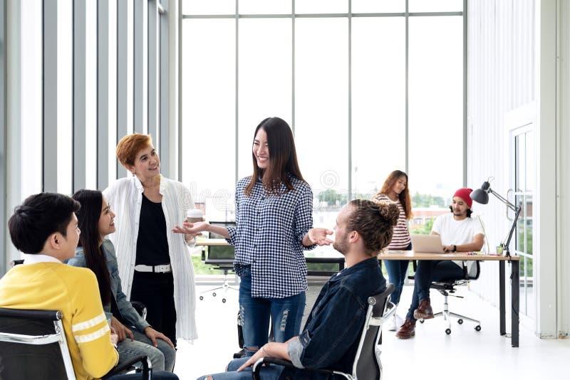 El grupo de equipo creativo multiétnico joven dedicó intercambio de ideas a la pequeña reunión mientras que se unía, siéntase y h fotos de archivo