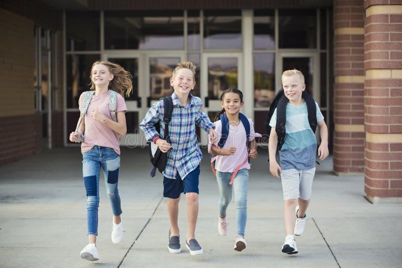 El grupo de escuela embroma el funcionamiento mientras que salen de la escuela primaria a finales del día foto de archivo