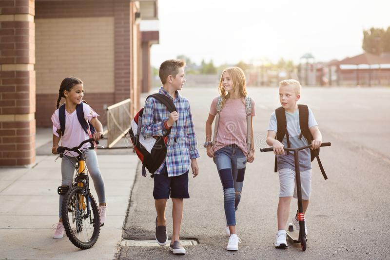 El grupo de escuela embroma hablar y caminar a casa de escuela junto fotografía de archivo