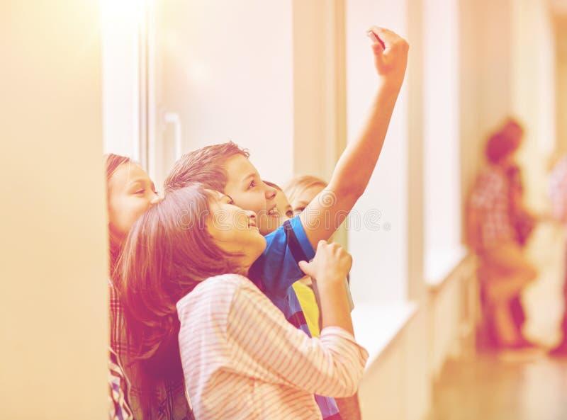 El grupo de escuela embroma tomar el selfie con smartphone imágenes de archivo libres de regalías