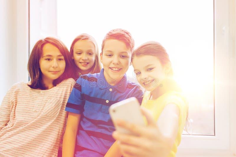 El grupo de escuela embroma tomar el selfie con smartphone imagen de archivo libre de regalías