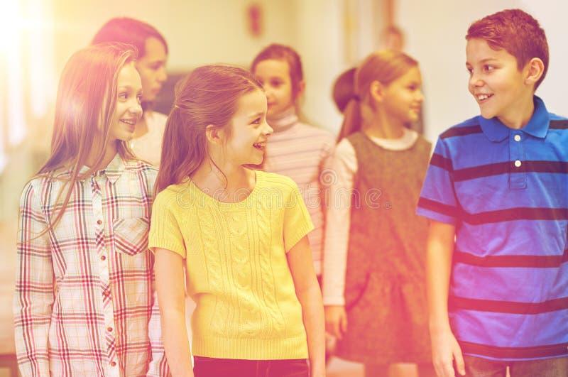 El grupo de escuela sonriente embroma caminar en pasillo imagen de archivo libre de regalías