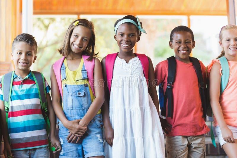 El grupo de escuela sonriente embroma la situación en fila foto de archivo