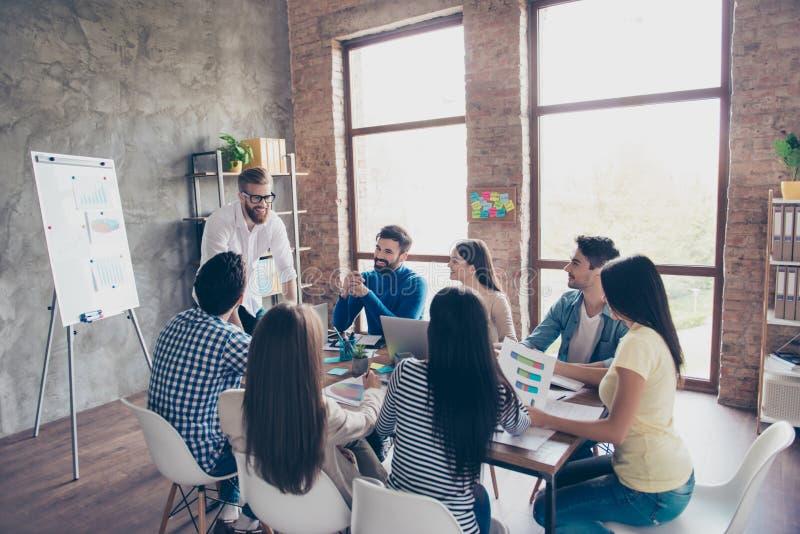 El grupo de estudiantes está discutiendo el proyecto de la universidad en agradable foto de archivo libre de regalías